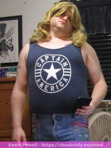 Kevin William Powell posing in fem shirt and jeans with wig and makeup