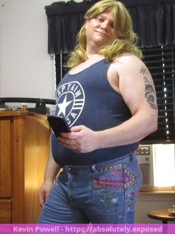 Kevin William Powell posing in fem shirt and jeans with wig and makeup in a different pose